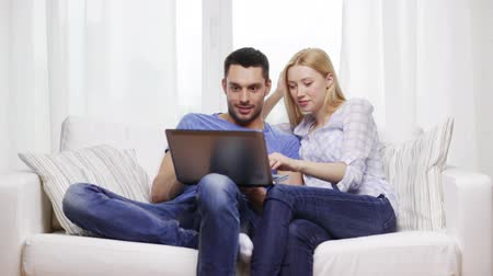 estilo de vida : home, technology and relationships concept - smiling couple with laptop computer at home