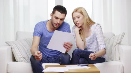 impostos : tax, finances, family, home and happiness concept - happy couple with papers and calculator at home