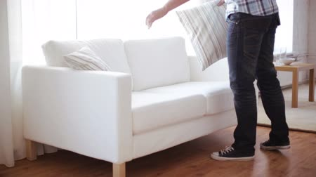 real : home, real estate and furniture concept - male decorating new home - putting pillows on sofa Stock Footage