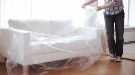 bútor : home, real estate and furniture concept - male putting down new sofa at home and taking polyethylene off