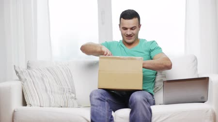 kutu : technology, home and lifestyle concept - smiling man with laptop and cardboard box at home Stok Video