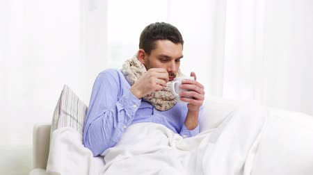 грипп : home, healthcare and medicine concept - ill man with flu drinking hot tea at home