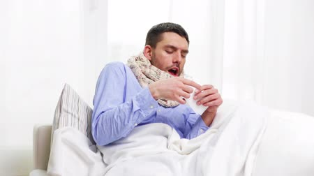 грипп : home, healthcare and medicine concept - ill man with flu at home sneezing and blowing nose