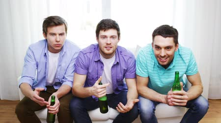 кричать : friendship, sports and entertainment concept - upset male friends with beer watching tv and clinking at home Стоковые видеозаписи