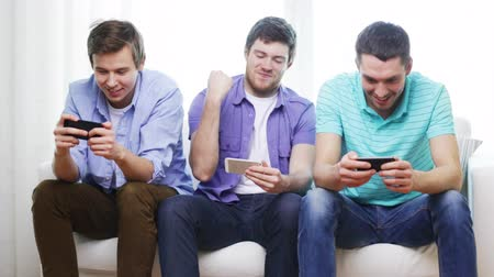három ember : friendship, technology and home concept - smiling male friends with smartphones at home