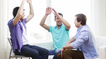három ember : teamwork, friendship and happiness concept - smiling male friends giving high five at home Stock mozgókép