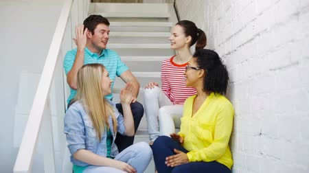 пять : education, gesture and happiness concept - smiling students making high five gesture sitting on staircase Стоковые видеозаписи