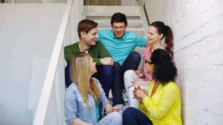 aluno : education, communication and happiness concept - group of smiling students sitting on stairs and talking