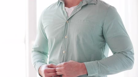 pansuman : dressing, clothing and casual concept - close up of man unbuttoning his shirt at home