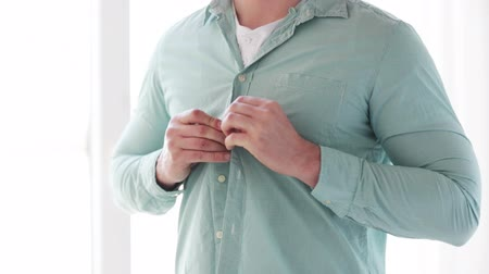 чистый : dressing, clothing and casual concept - close up of man buttoning his shirt at home Стоковые видеозаписи