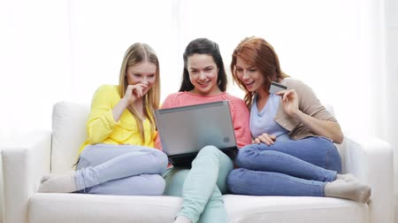 három ember : friendship, money, technology and internet concept - three smiling teenage girls with laptop computer and credit card at home