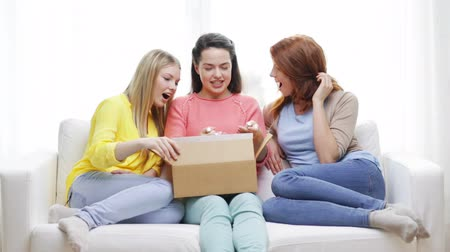 tektura : transportation, post and friendship concept - three smiling teenage girls opening cardboard box at home Wideo