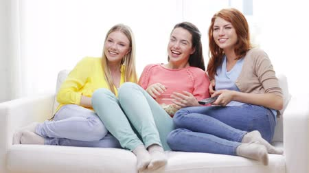 három ember : home, technology and friendship concept - three smiling teenage girls watching tv at home and eating popcorn Stock mozgókép