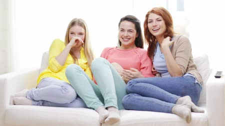 дружба : home, technology and friendship concept - three smiling teenage girls watching tv at home and eating popcorn Стоковые видеозаписи