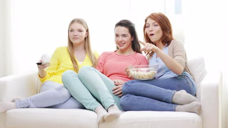três : home, technology and friendship concept - three smiling teenage girls watching tv at home and eating popcorn Vídeos