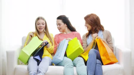 tizenéves lányok : shopping and lifestyle concept - three smiling teenage girls with many shopping bags at home
