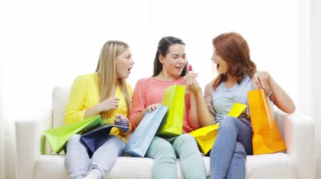 nehet : shopping, friendship and lifestyle concept - three smiling teenage girls with many shopping bags at home