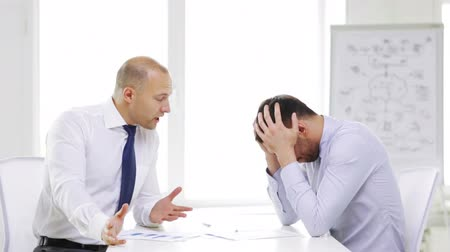 excuses : business, partnership, finances and office concept - two serious businessmen holding papers and talking in office