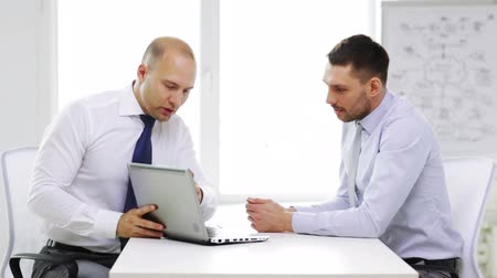 two people talking : business, technology, finances and office concept - two smiling businessmen with laptop computer in office