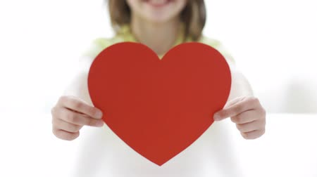 holding : love, home, happiness, childhood and people concept - close-up of smiling girl with red paper heart at home