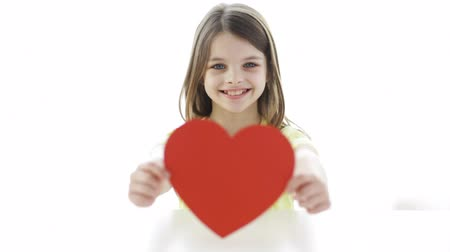 dövmek : love, home, happiness, childhood and people concept - smiling girl with red paper heart at home