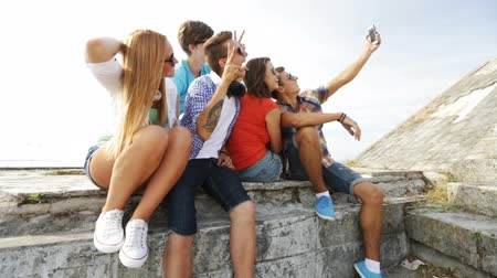 group : summer vacation, friendship, street life, technology and people concept - group of smiling teenagers hanging out and making selfie outdoors Stock Footage