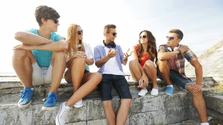 gençlik kültürü : summer vacation, friendship, street life, technology and people concept - group of smiling teenagers hanging out and chatting outdoors Stok Video