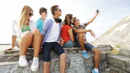 korkak : summer vacation, friendship, street life, technology and people concept - group of smiling teenagers hanging out and making selfie outdoors Stok Video