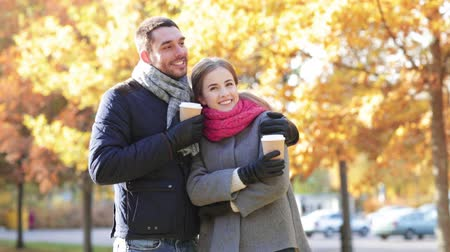 испанец : love, relationship, season, friendship and people concept - smiling couple with coffee cups in autumn park