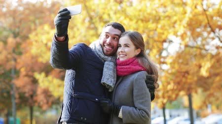 társkereső : technology, relationship, family and people concept - smiling couple taking selfie with smartphone in autumn park
