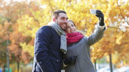 smartfon : technology, relationship, family and people concept - smiling couple taking selfie with smartphone in autumn park