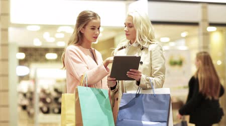 покупка товаров : sale, consumerism, technology and people concept - happy young women with tablet pc and shopping bags talking in mall
