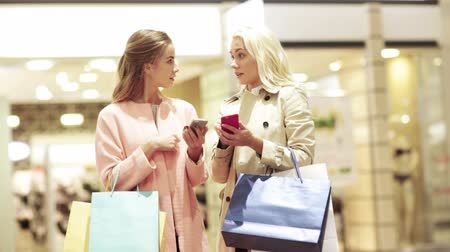 покупка товаров : sale, consumerism, technology and people concept - happy young women with smartphones and shopping bags talking in mall