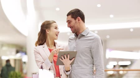 удовлетворенный : sale, consumerism, technology and people concept - happy young couple with shopping bags and tablet pc computer talking in mall