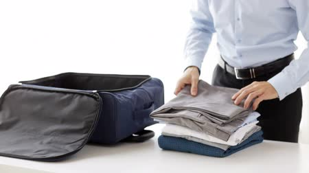 kalhoty : business, trip, luggage and people - close up of businessman packing clothes into travel bag