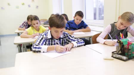 sınıf : education, elementary school, learning and people concept - group of school kids with pen and papers writing test in classroom Stok Video