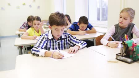 učit se : education, elementary school, learning and people concept - group of school kids with pen and papers writing test in classroom Dostupné videozáznamy