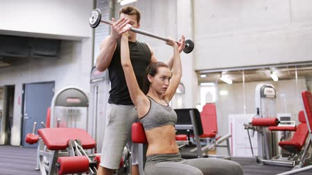eğitici : sport, fitness, lifestyle, weightlifting and people concept - young woman and personal trainer with barbell flexing muscles in gym