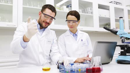 science, chemistry, technology, biology and people concept - young scientists with pipette and flask making test or research in clinical laboratory