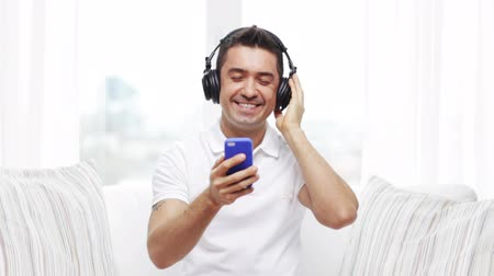 sluch : technology, people, lifestyle and distance learning concept - happy man with smartphone and headphones listening to music at home