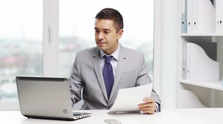 gerente : business, people, paperwork and technology concept - smiling businessman with laptop computer and papers working in office