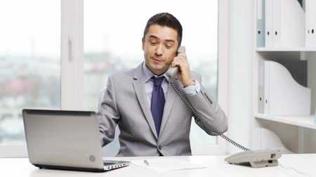 business man : business, people, paperwork and technology concept - smiling businessman with laptop computer and papers calling on phone in office Stock Footage