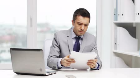 számla : business, people, paperwork and technology concept - businessman with laptop computer and papers working in office