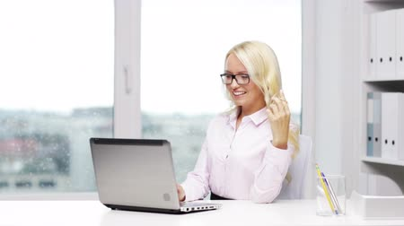 titkár : education, business and technology concept - smiling sexy woman secretary or student in eyeglasses with laptop computer typing in office Stock mozgókép