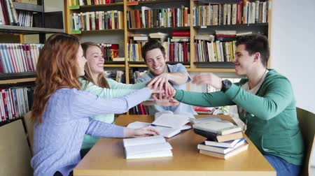 insan eli : people, knowledge, education and school concept - group of happy students preparing to exam and putting hands together on top in library Stok Video