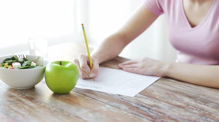 planları : healthy eating, dieting and people concept - close up of young woman hands writing diet plan at home