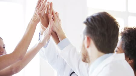 médicos : gesture profession people teamwork and medicine concept  group of happy doctors meeting and making high five gesture at hospital Vídeos