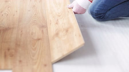 устанавливать : repair building floor and people concept  close up of man installing wood flooring