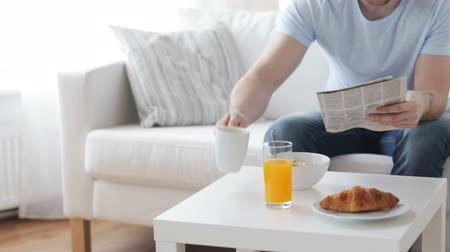 kruvasan : leisure breakfast and people concept  close up of man reading newspaper and drinking coffee at home Stok Video