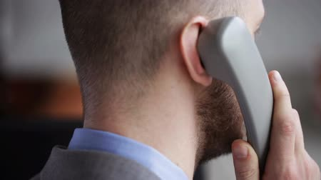conversando : people business technology and office work concept  close up of businessman calling on phone
